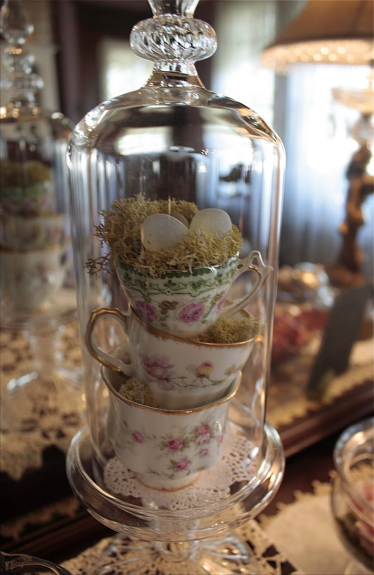 Teacups stacked in a narrow  cloches or tall glass jars make lovely easter or tea party decoration.