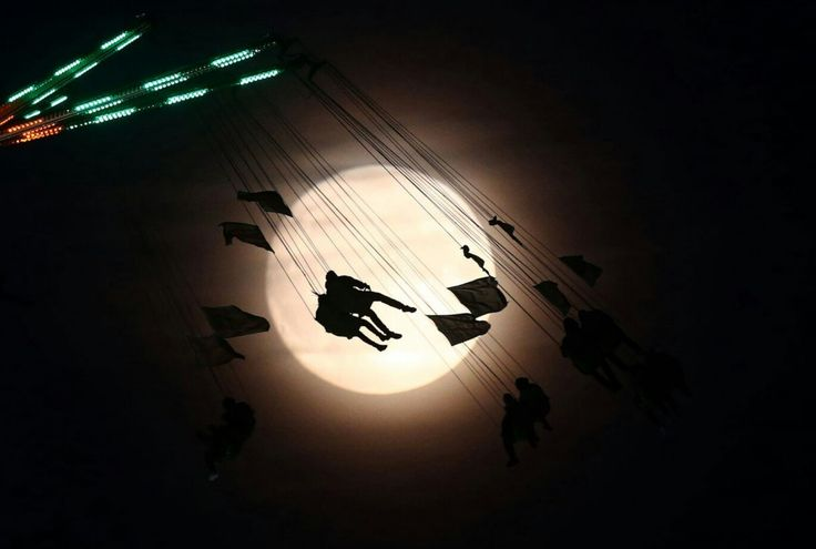 People on a funfair ride are silhouetted against the moon a day before the supermoon spectacle, in London.