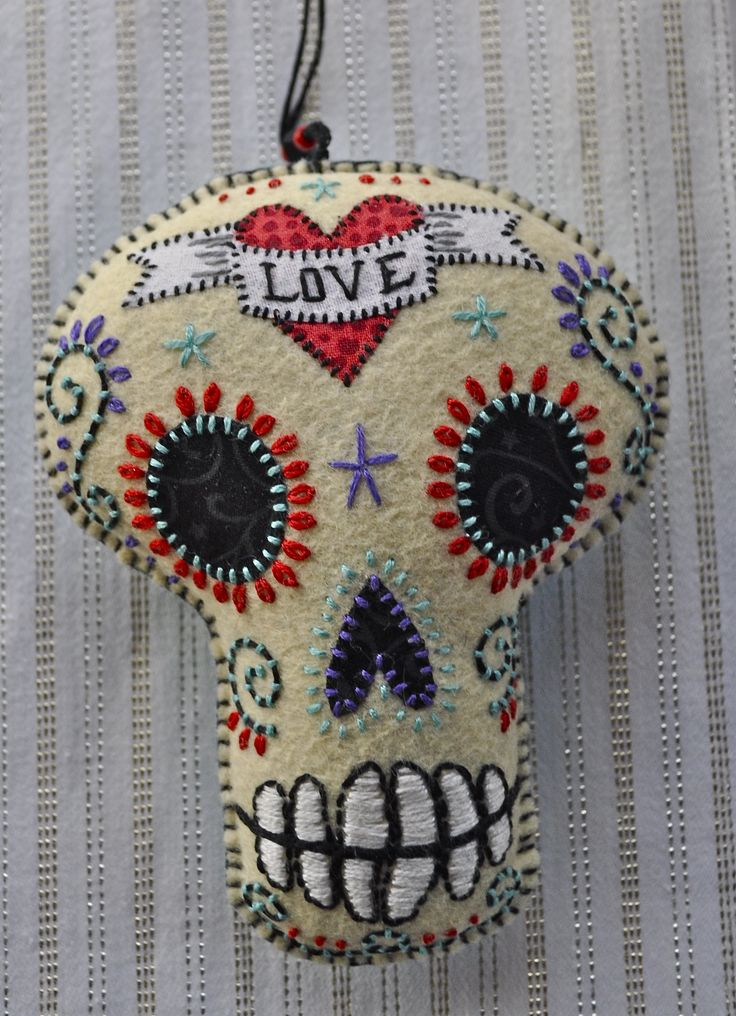 Felt calavera with 'Love' in a red heart on the forehead of a skull.  #eldiadelosmuertos #dayofthedead #sugarskull