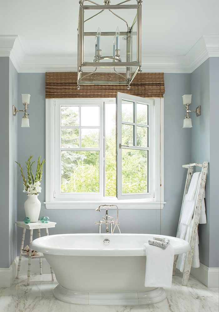 A Hamptons-style home evolves with the needs of its homeowners and their all-gal crew. | Colorado home design and architecture, interior design, luxury homes, contemporary home design, modern home design, luxury bathroom design, light blue bathroom, large white bath tub