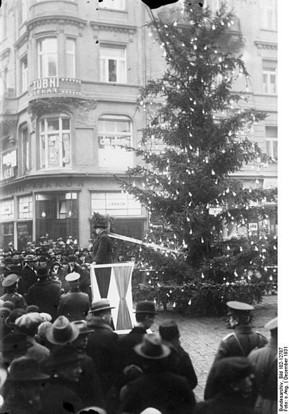 An early example of a public (outdoor) Christmas tree in Europe; public Christmas celebration for the unemployed in Prague, First Czechoslovak Republic, in 1931.