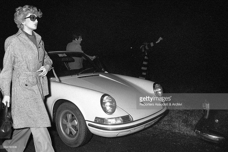 Italian singer Mina Mazzini and Italian actor Corrado Pani getting out of their car. Italy, 1960