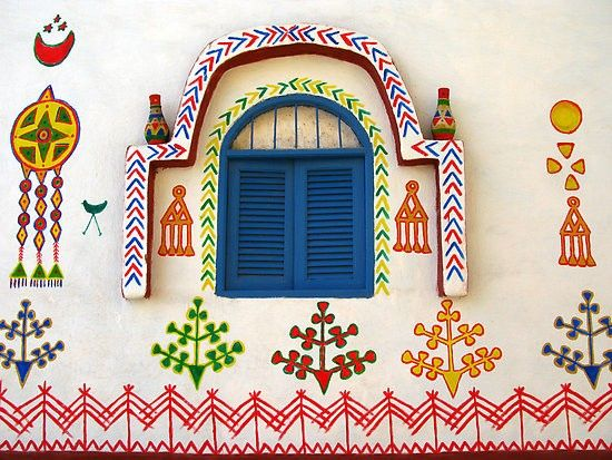 Nubian Village in Aswan ... the bright little paintings surrounding this blue shuttered window add tons of charm