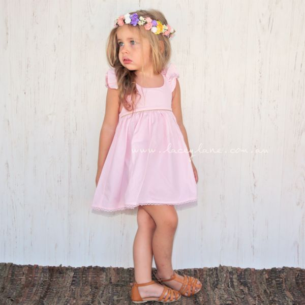 Hailey Dress - Baby Pink fabric -Detailed gold piping on bodice -Gold beading on back straps -Delicate lace on bottom hem -Elastic back -Belt Loops -100% cotton -Regular fit Model is wearing a size 2. Nora Flower Crown sold separately.