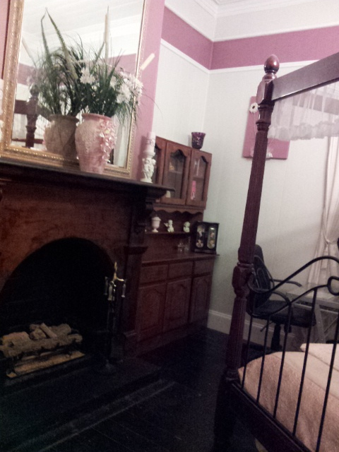 Queenslander home - Bedroom 2 - daughters room - gas log fireplace with red cedar surround - trim done in tearose colour.