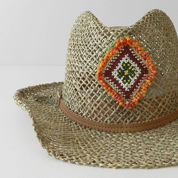 Sombrero cowboy ajustable, decorado con motivo étnico central en rocalla y terminación cadenas metálicas antiguas. Realizado artesalmente y fabricado en España. Composición fibras vegetales.