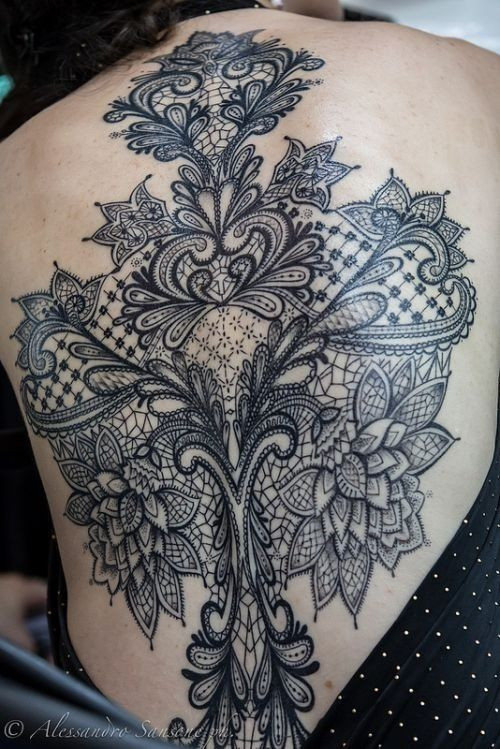 Beautiful delicate black linework tattoo on back; floral, lace and mandala designs all weaved together.