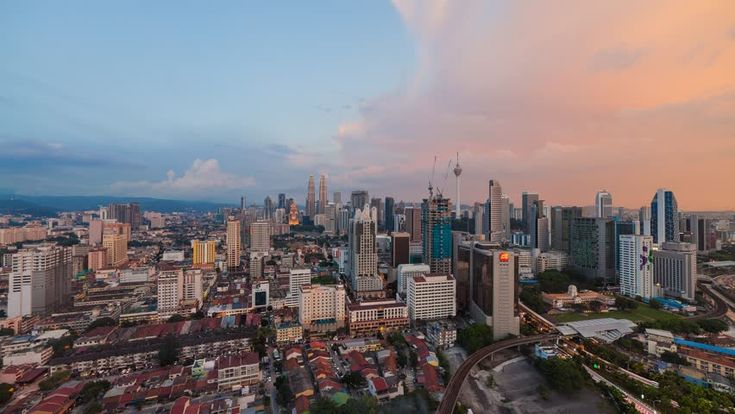 Beautiful sunset view of Kuala Lumpur city with dancing clouds and golden lights and moon rise. Time lapse. Slide effect.