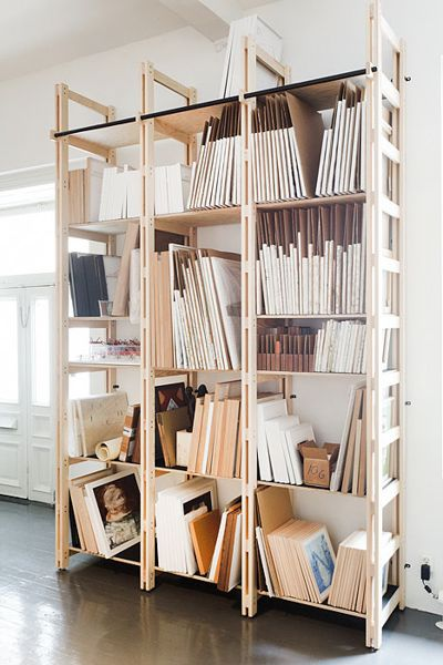 home office inspiration with lots of shelves and storage. artist studio. use sheets of cardboard to separate and protect canvases.