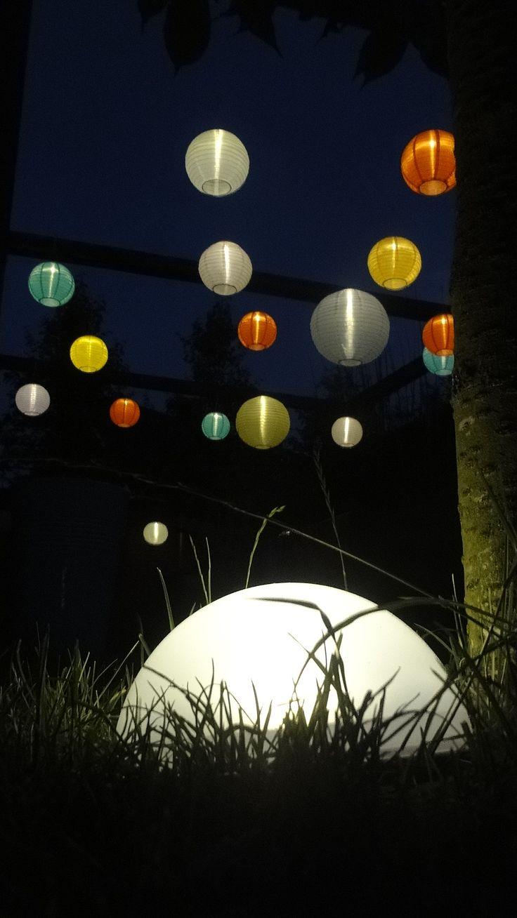 15 IKEA Solvinden lampionnen aan een netwerk van vliegertouw gespannen aan de hoogste balken van de pergola. Overdag laden de zonnecellen zich op. Wanneer het donker wordt gaan de lampen vanzelf aan en blijven schijnen tot het bijna weer licht wordt. In het gras ook een lamp op zonne-energie. Zo hebben we onze tuin deze zomer gratis verlicht.
