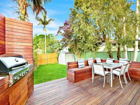Decked back yard area, natural wood bench seating, grill