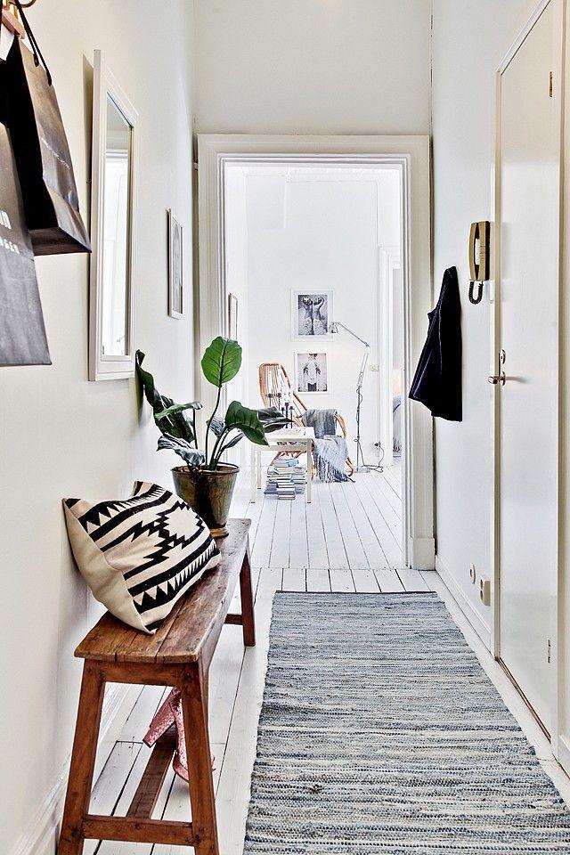 Entrée stylée avec un coussin graphique, une plante et un banc de bois dont la barre centrale maintient les chaussures.