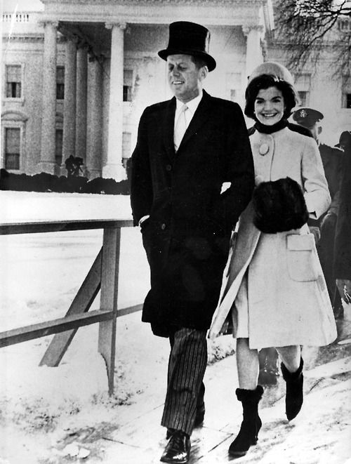On January 20, 1961, walking arm in arm together, President John F. Kennedy and his wife, First Lady Jacqueline Kennedy on their way to the reviewing stand to watch the inauguration parade shortly after the young president's inauguration as the 35th President of the United States. In the background is their new home, The White House. At age 43, he was the youngest man to be elected president, and Jackie, at age 31, was the third youngest First Lady.