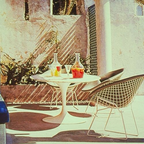 Elegant Harry Bertoia White Diamond Chairs Set Up On A 1960s Patio With Table