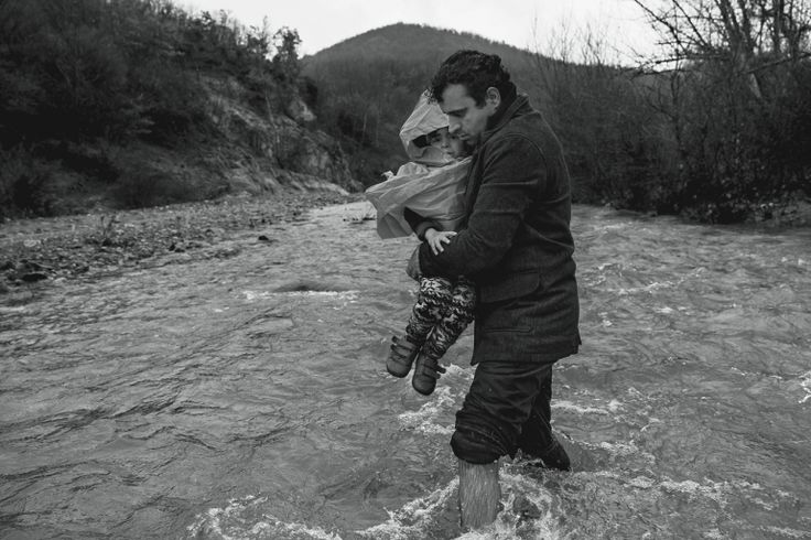 Refugees in camp at border of Greece and Macedonia near town of Idomeni. The refugees are being stopped from moving beyond Greece and have been languishing in the rain and the mud and the cold with insufficient food and medical care while sleeping in small tents. A couple thousand refugees walked overland to get around border fence and into Macedonia. Crossing a river along the way.by James Nachtwey