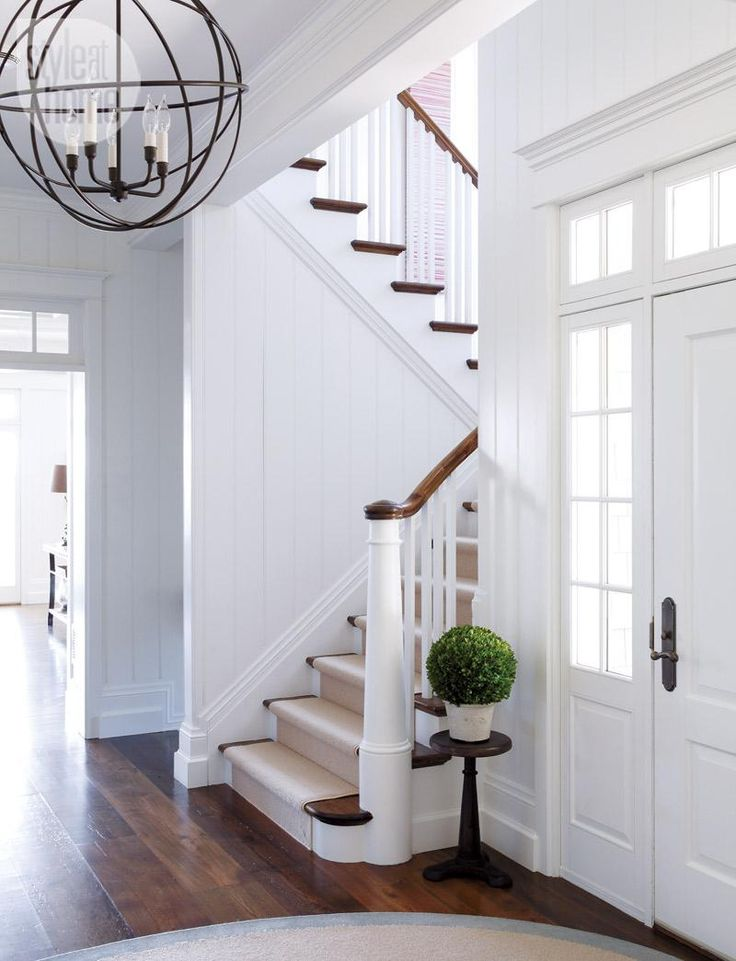 Wooden floor, white walls, white stairs, wooden bannister and central globe ceiling pendant