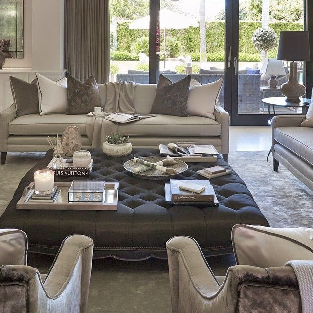 Grey, silver, white Lounge/living area with glass doors leading outside. Couch,pillows,coffee table, armchairs.~ Sej