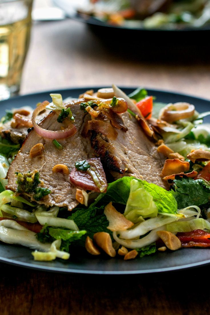NYT Cooking: There are a lot of ingredients in this bright and bold-tasting pork salad recipe; they add up to a vibrant dish you can serve warm or at room temperature to a spice-loving crowd. Lean pork tenderloin is marinated with chiles, ginger root and cilantro, grilled or broiled, then combined with cabbage, fresh herbs and nuts and coconut for richness. A bit of reserved marina...