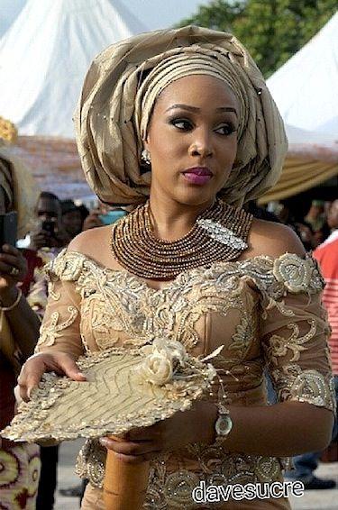 Nigerian bride in gold gele, jewelry beads, aso ebi African fabric Ankara lace dress for wedding.