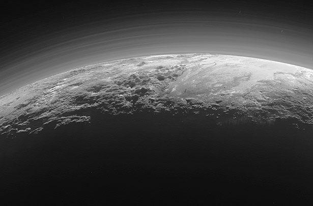 Ein spektakulärer Anblick: Wenn man es nicht wüsste, könnte man diese Aufnahme für ein Bild der Erde im Gegenlicht halten. Doch zu sehen ist hier die Oberfläche des Zwergplaneten Pluto – aufgenommen von der Raumsonde New Horizons. Mit seinen zerklüfteten Gebirgen, den frostigen Ebenen und nebelverhüllten Landschaften erscheint der eisige Himmelskörper verblüffend erdähnlich.