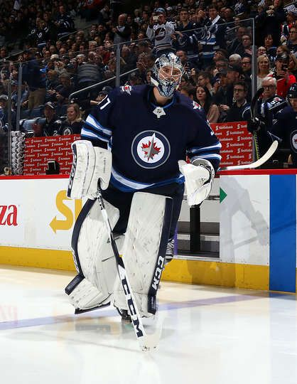 WINNIPEG, MB - DECEMBER 27: Goaltender Connor Hellebuyck #37 of the Winnipeg Jets hits the ice prior to puck drop against the Edmonton Oilers at the Bell MTS Place on December 27, 2017 in Winnipeg, Manitoba, Canada. (Photo by Jonathan Kozub/NHLI via Getty Images)