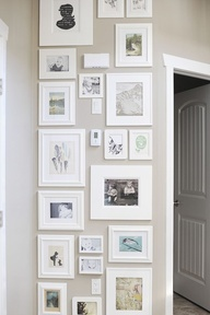 Im moving to do this in my house soon! Frame all your photos in the same color like black or white, or in the same material like aluminum or wood. Eventually, they will look like a collection to keep intact or break up into smaller areas depending on where you live.  ---  hallway upstairs