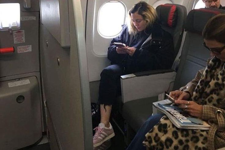 """She may be the Queen of Pop, but Madonna opted to shun first class travel in favour of economy on a recent flight to Portugal. The 59-year-old shocked passengers after she jetted out of the capital to Lisbon on Halloween. The Material Girl singer was pictured using her phone in a window seat on the Air Portugal flight in what appeared to be economy class. The picture was taken by a fellow passenger who captioned the image: """"If you fly with M! London – Lisbon. 2017.10.31."""""""