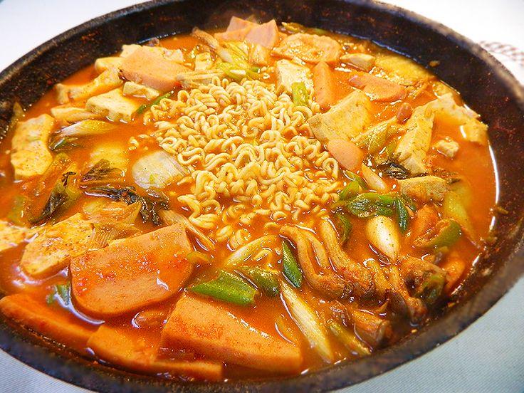 부대찌개 – Budae Jjigae. Diz a lenda que a comida era escassa logo após a Guerra da Coreia. Algumas pessoas utilizavam restos de salsicha, presunto enlatado, e presunto de porco condimentado encontrados na área dos quartéis e os colocavam num cozido apimentado. Hoje em dia, é uma delicadeza popular apreciada por muitos sul-coreanos. É um cozido de kimchi que contém macarrão ramen, carne moída, salsichas, cebolas, tofu, cogumelos e muitos outros ingredientes.