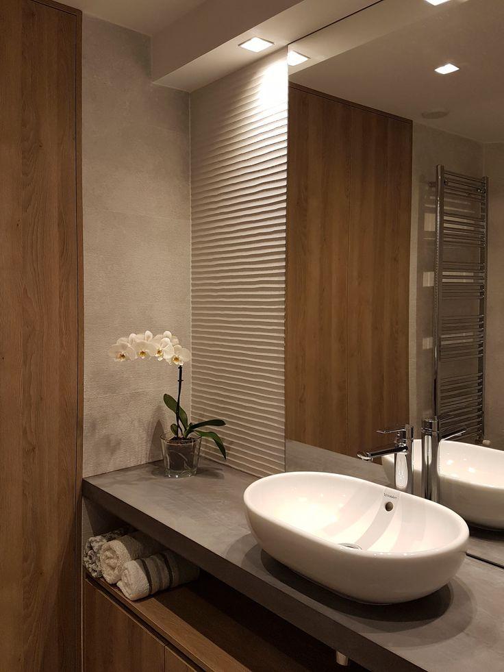 Baño minimalista. Encimera en microcemento. Revestimiento en porcelánico imitación hormigón. Lavabo ovalado de sobre encimera. Mobiliario en imitación madera. Proyecto diseñado y ejecutado por AZ Diseño.