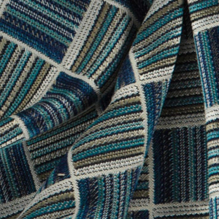 A geometric jacquard furnishing fabric available in a multicoloured - aqua - blue colourway. This article has a synthetic composition, and is suitable for curtains and upholstery.