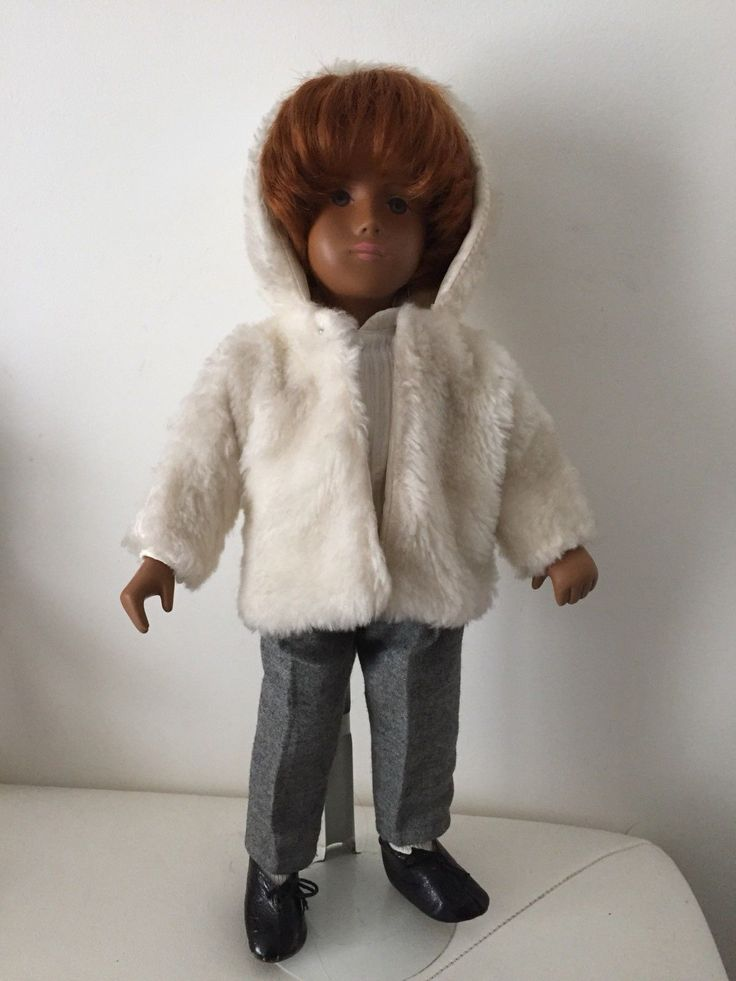 Wearing a white furry hooded jacket with grey flannel trousers.