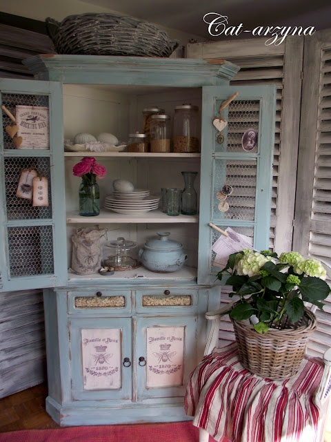 Check out the crown moulding and chicken wire doors, antiqued advertisement on the doors---great corner cabinet redo