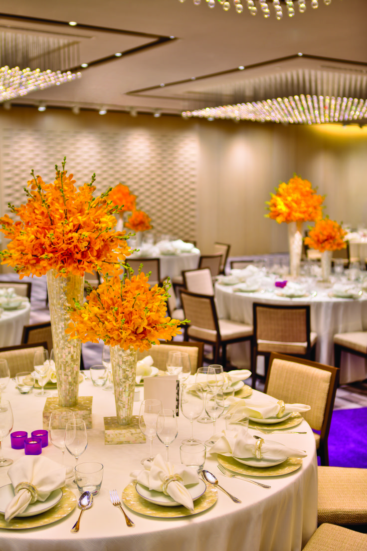 Vivid and charismatic orange floral centerpieces at a wedding at Grand Hyatt Singapore.