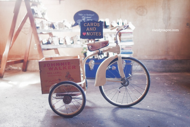 A Vintage & Pretty cards and notes tricycle with a ladder and rustic plank wedding favours display in the background.    Photography by Candy Capco