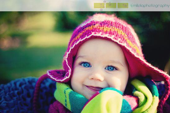 un bebe aux grand yeux bleus sourit pour une seance photo de sa maman