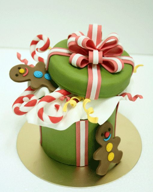 We love this Christmas Cake decorated as a gift box filled with gingerbread men & candy canes. #cake #christmas