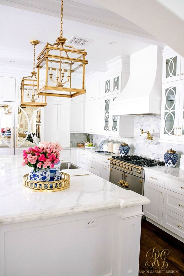 This is what kitchen dreams are made of! White transitional kitchen with gold, blue and pink decor touches. Trend Alert Pink and Blue - Randi Garrett Design