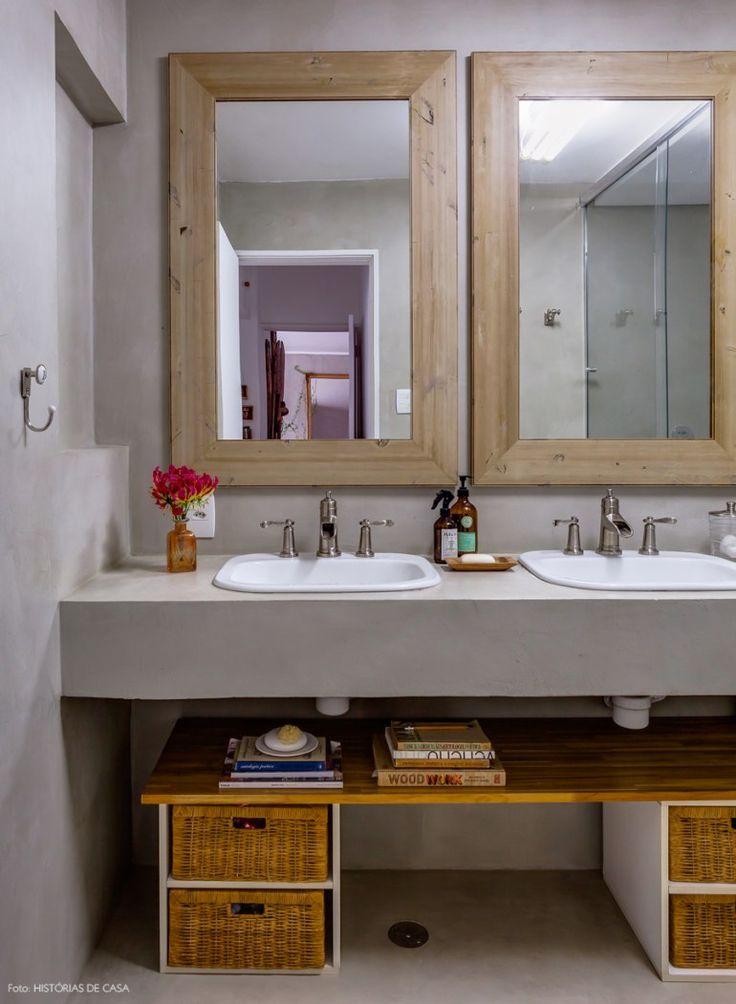 Banheiro com piso e bancada de cimento queimado e espelhos com moldura de madeira.