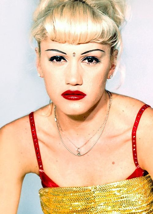 The gorgeous Gwen Stefani poses with her trade mark bindi and bright lips. By curling the full fringe in and bringing the rest of her hair up she makes it more flattering to her face #gwenstefani #hair