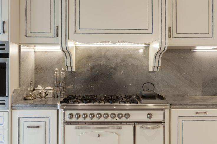 Stylowa, biała, drewniana kuchnia ze srebrnymi zdobieniami, szarym blatem i ścianą    Stylish, white, wooden kitchen with silver ornaments, gray top and wall