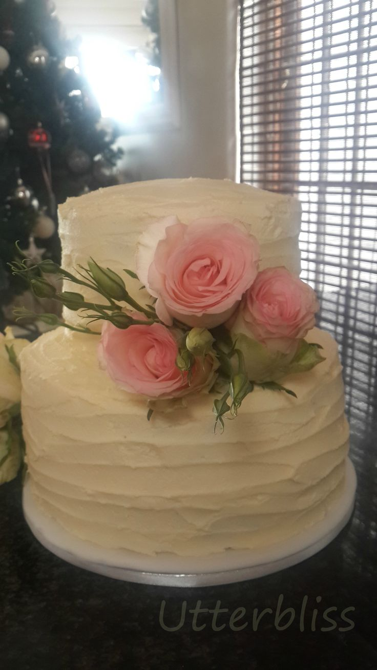Butter icing wedding cake with fresh flowers.