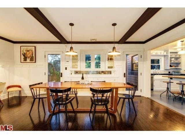This LA dining room has dark wood flooring, simple dining table with wooden chairs, exposed wooden ceiling beams, dual hanging light fixtures, built in cabinets and subtle wainscot.