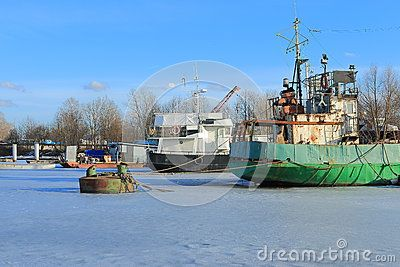 Fishing trawlers soldered to the ice in the Neva Bay on a sunny day. Saint-Petersburg, Russia