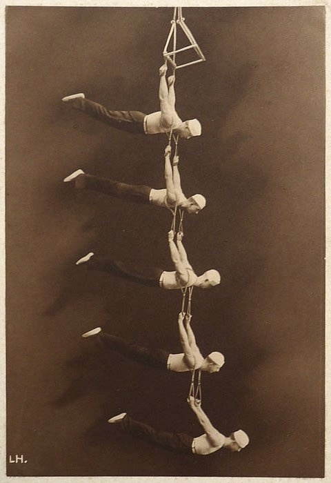 this is an amazing ladder of men!  Suspended by suspenders, Vintage Circus Performers. Holy Crap that's a lot of planges.