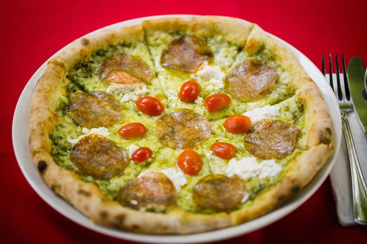 """""""Pizza con Rucola Pesto."""" A hand-tossed crust that's simultaneously crispy, chewy and light. Topped with a delicious rocket-pine nut pesto, balls of creamy mozzarella, thinly sliced salami, ricotta and juicy cherry tomatoes."""