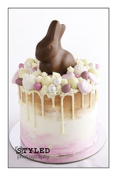 Vanilla Cake, with buttercream Neapolitan watercolor swirl. with Easter embellishments, chocolate eggs and chocolate drizzle drip. Topped with a Lindt chocolate bunny