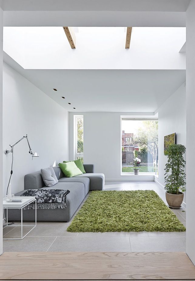 Modern danish living room: The sofa is from Hay, the green carpet is from Møbelhuset in Ry. The stones on the floor are from Flise Bent.