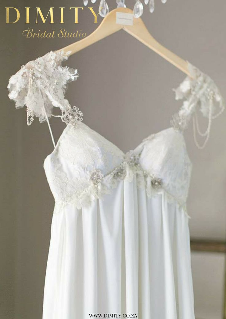 Christill's Dimity gown featuring an empire line embellished with lace motifs, pearls & metal crochet flowers.