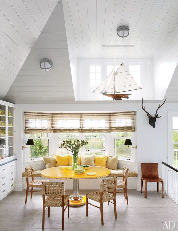 In the breakfast area of a Southampton beach house by interior designer David Netto, a set of mahogany-and-rattan chairs purchased at Christie's joins a yacht table by Soane Britain | archdigest.com