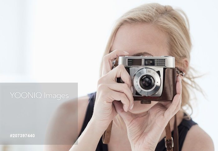 Yooniq images - Woman taking photo with digital camera